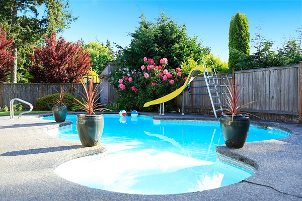 Fenced backyard with small beautiful swimming pool and playground
